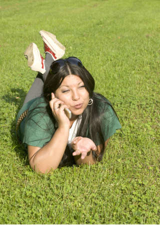 Beauty young woman lies on lawn and speaks by phone photo