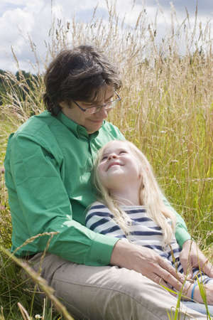 father with daughter on meadow in summer Stock Photo