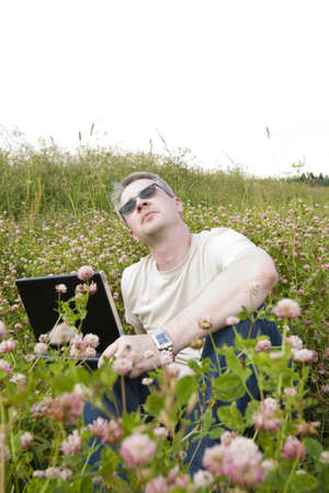 thoughtful man with laptop on meadow Stock Photo