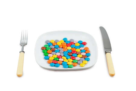 Knife, plug and plate with  lot of multi-coloured tablets