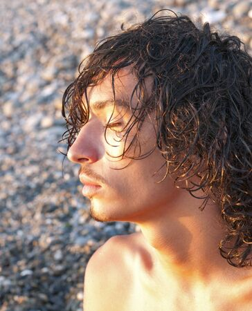close up  profile of young man meditates on seacoast