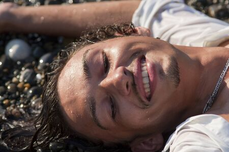 young smiling man lies on seacoast