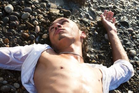 seacoast: young man lies on seacoast
