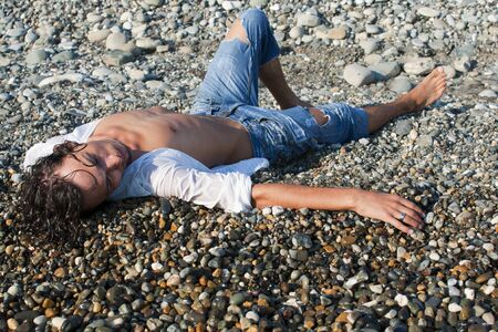 young man lies on coastline
