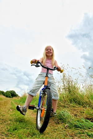 Little girl on bicycle on meadow photo