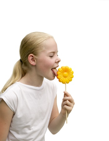 Young girl eating a flower shaped lollipop isolated on white background Stock Photo
