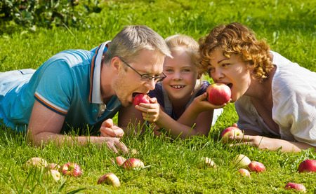 young pair with child bites apple, lie on a grass Stock Photo
