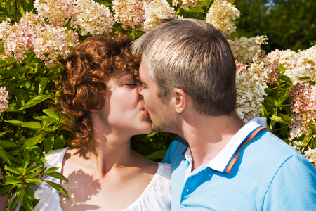 young pair kisses in a flowers