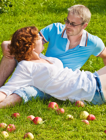 young pair sitting on a grass with apples