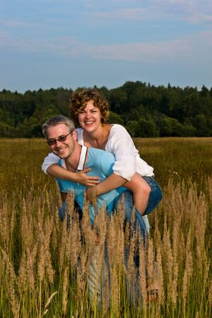 man holds  woman on hands on a meadow Stock Photo