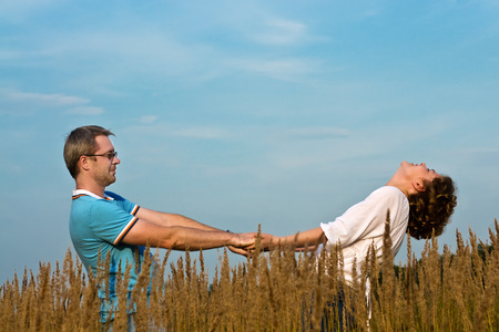 young pair holds hands on a meadow Stock Photo