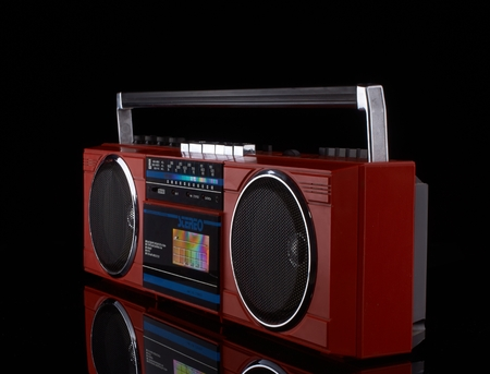 Vintage red boom box on black background with reflection