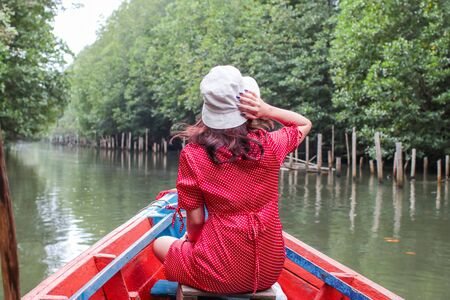 Back of a Senior Lady Tourist on a Wooden Boat on a River. Location is Tung Prong Thong Nature Reserve, Thailand.