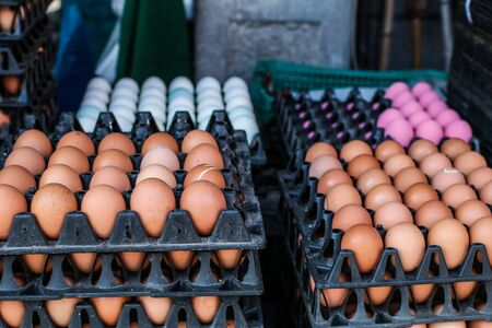 Huevos frescos de granja en las cajas de cartón a la venta en el mercado. Foco seleccionado.