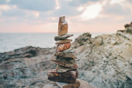 A stack of round stones standing on the shore of a sea Rocky coast at Khao Laem Ya Mu Ko Samet National Park Rayong, Thailand in sunset time Standard-Bild