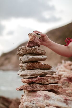Womans hand puts Pyramid stack of round stones standing on the shore of a sea Rocky coast at Khao Laem Ya Mu Ko Samet National Park Rayong, Thailand in sunset time