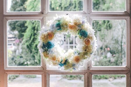 A wreath of spring flowers of blue and lilac hanging on a wooden door Foto de archivo