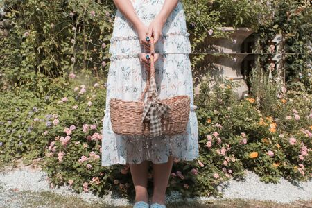 Woman holding basket ready to start picking up herbs and flowers on her garden. Half empty basket. Woman in flowery white colorful dress