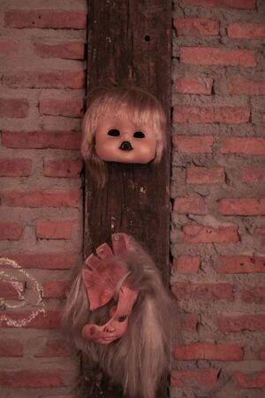Broken Doll Face and Head hanging on brick wall decoration for Halloween party Reklamní fotografie