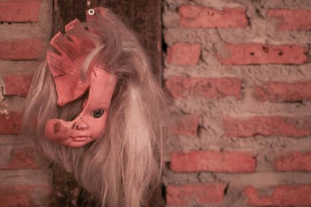 Broken Doll Face and Head hanging on brick wall decoration for Halloween party Archivio Fotografico - 130541852