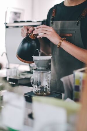Close up image Young male barista pouring boiling water from kettle for filter coffee Drip brewing, filtered coffee, or pour-over is a method which involves pouring water over roasted, ground coffee beans contained in a filter.