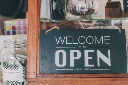 Open sign board close-up through the glass of a window at coffee shop door. Shallow depth of field.A business vintage sign that says Come in Were Open on Cafe  Restaurant window. Image of abstract blur restaurant with people. Restaurant with customer for background usage