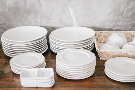 Clean Dishes & Other Tableware placed on a wooden shelf Wooden shelf template isolated on white wall background which on set stacked white bowls and plates as items tableware for decorated interior or montage of your product on shelf with copy space. Stok Fotoğraf