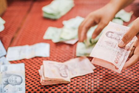 Human hand holding Thai banknotes Close up hands counting of thousansds Thai baht money.Close up Human counting Thai banknote, richman count and holding hundred. Baht bills on table Stock Photo
