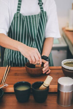 Japanese tea ceremony,Matcha tea prepared with bamboo whisk Flat lay matcha latte preparation concept.making matcha tea mix green powder in a mug on a background of coffee tools.