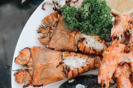 Primo piano di un delizioso piatto di pesce alla griglia. Vassoio di cozze, gamberi, gamberi e vongole con salsa di immersione piccante e acida che è piena di sapore di pesce tailandese.