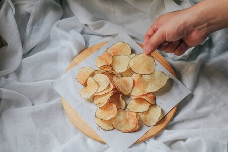 Hand pick up pieces of fresh homemade deep fried crispy  potato chips on a wooden tray, top view. Salty crisps scattered on a table for a tasty snack break and party movie time. Banco de Imagens