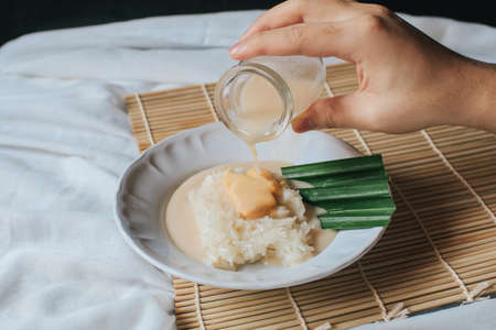 Hand pouring coconut milk durian creamy sauce in Thai sweet sticky rice with durian,glutinous rice is a delicious sweet thai food on table.One of most famous Thai dessert in summer