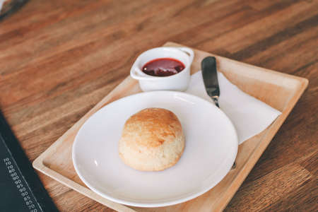 Close-up Homemade delicious English scone set with strawberry jam on the table. Horizontal,copy space for text, selective focus.