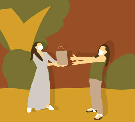 Young beautiful girl stand in autumn park wearing face mask with her friend and receiving a paper bag with gift for holiday party celebration. Social distancing lifestyle