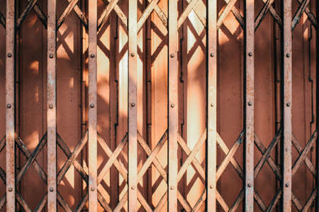 Morning sunlight and shadow on the closed metal steel door - Folding door texture pattern and background.Expanded metal sliding gate. Old style grunge metal door. 写真素材