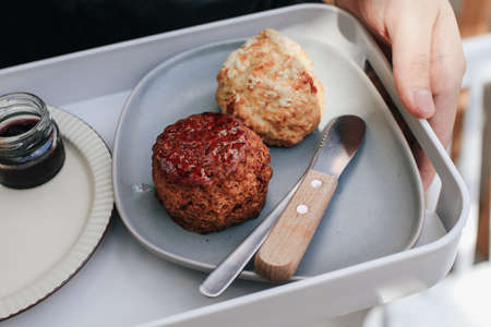 Delicious scones with Strawberry Jam, Clotted Cream and butter knife on a tray.