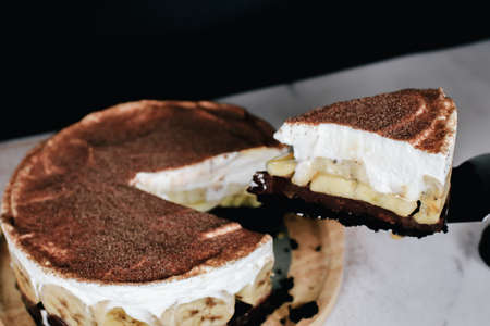 Banoffee cake with bananas, whipped cream, chocolate, caramel, coffee and toffee in cafe restaurant