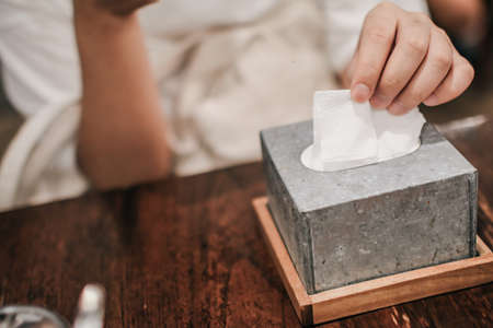 Man taking paper tissue from holder in restaurant. Caffe or restaurant on background. 写真素材