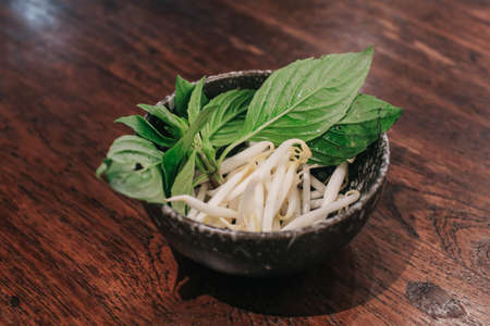 Fresh basil leaf and bean sprouts in white plate on a wooden table. Is a side dish of Noodles, top view.