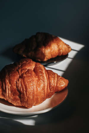 Croissants on a dark background in the morning light, sunlight shadow. Morning breakfast concept. Copy space.