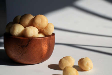 Macadamia nuts in wooden bowl on white table with sunlight and shadow. Macadamia nuts are a source of protein packed with healthy vitamins. 写真素材