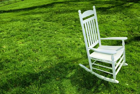 contrasty: White rocking chair on the lawn. Stock Photo
