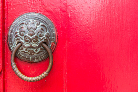 holder for door knocker and copper nails on a red door. photo