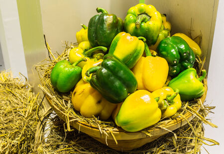 Wicker basket full of sweet green, yellow and red bell peppers . photo