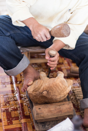 A craftsman working wood the oldfashioned way, hammer and chisel used to carve shape into a piece of wood. photo