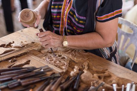 guild: A craftsman working wood the oldfashioned way, hammer and chisel used to carve shape into a piece of wood.
