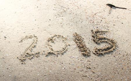 Year 2015 number written on sandy beach. photo