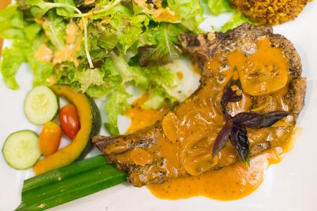 grilled pork chop: juicy grilled pork chop (neck cut) with greens.