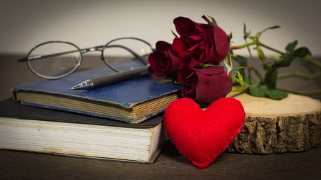 Roses on old books and glasses, small heart on wood timber photo
