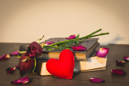 Roses on old books and small heart, vintage style. photo